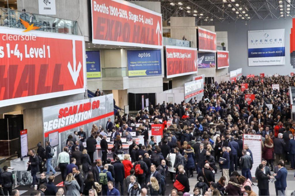 Foto tirada na NRF 2020, em que há os estandes dos expositores e muitas pessoas passando pelo loca. Já placas em vermelho penduradas, indicando os locais das palestras e em quais andares estão ocorrendo.